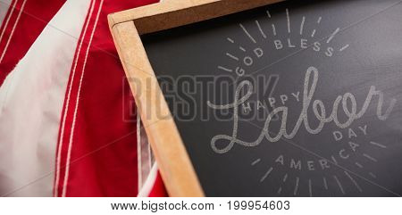 Composite image of happy labor day and god bless America text against american flag and slate