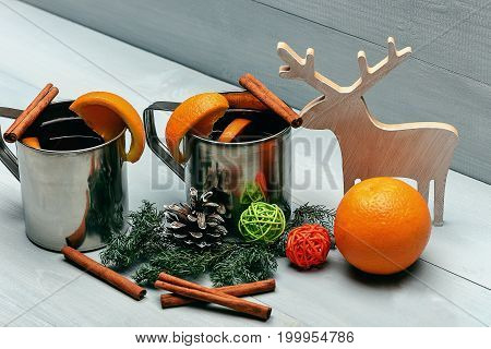 hot drink of mulled wine or tea with cinnamon spice stick in metallic mug near christmas decorative wood deer ball orange fruit and pinecone on grey wooden background