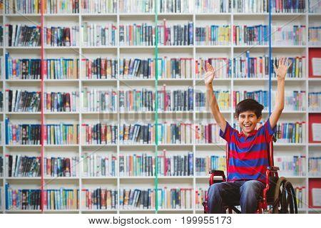 Boy in wheelchair in school corridor against multi colored bookshelf in library