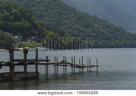 Old wood jetty lake with green mountain at nikko chuzenji japan.