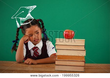Graduation hat vector against unhappy schoolgirl looking at books stack and apple against chalkboard
