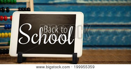Digital image of back to school text against digital tablet by abacus
