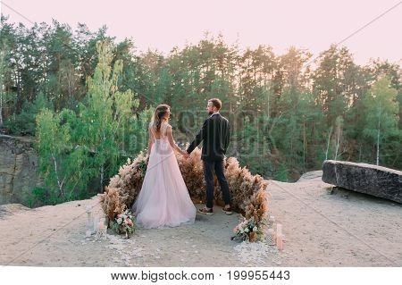 Newlyweds Holding Hands At The Edge Of The Canyon And Couple Looking Each Other With Tenderness And