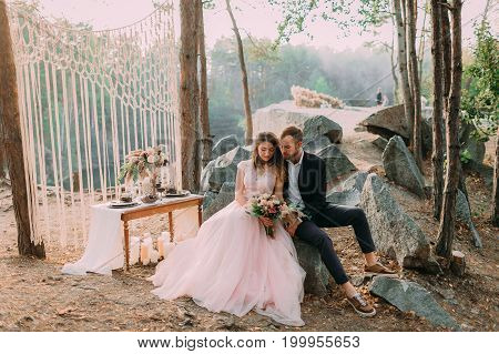 Attractive Couple Newlyweds, Happy And Joyful Moment. Man And Woman In Festive Clothes Sit On The St
