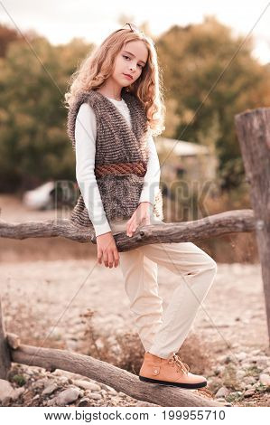 Beautiful teen girl 12-14 year old wearing trendy autumn clothes posing at countryside. Looking at camera.