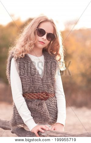 Stylish teen girl 14-16 year old wearing fur vest and sun glasses outdoors over autumn trees. Looking at camera.Childhood.