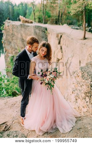 Happy Newlyweds Embracing. Man In Tuxedo And Woman In A Pink Wedding Dress Is Posing On Nature. A Ce