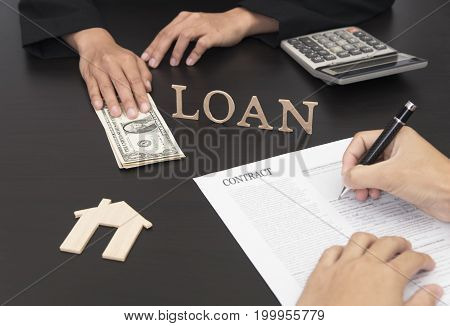 hand sign document contract for loan to buy home.