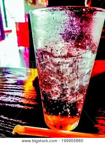A closeup of a colorful tall drinking glass full with ice on a table.