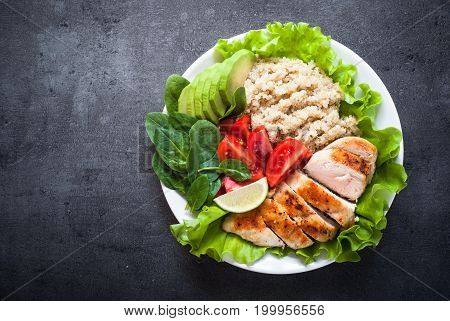 Balanced nutrition. Fresh salad from quinoa chicken breast avocado spinach lettuce and tomatoes. Healthy food. Portion plate