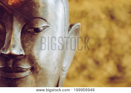 Close Up Face On Buddha Head Statue With Bokeh Background