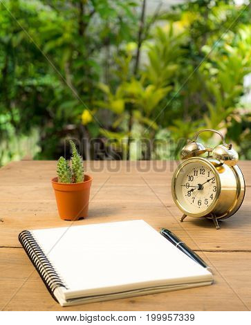 Blank notebook with vintage alarm clock and black pen and cactus on wood table. The background is green from tree and light bokeh