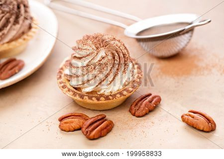 Mini tart with whipped cream sprinkled with ground cinnamon