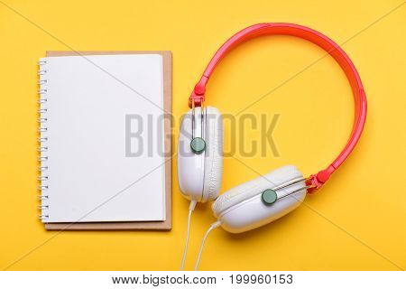 Music Accessories And Note Taking Concept. Modern Earphones