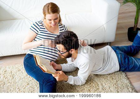 A portrait of a future father reading a book