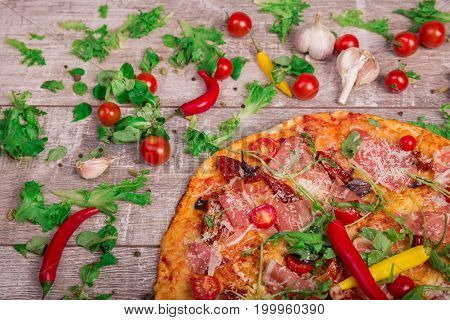 A view from above on a tasty prosciutto pizza with cherry tomatoes, chili peppers, and salad leaves. Delicious bright dish on a rustic wooden table background. Italian cuisine. Cooking concept.
