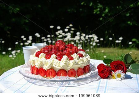 Summertime with strawberry cake and two mugs on a table in a garden