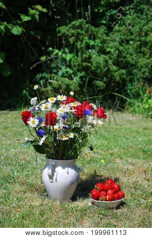Summer flowers in a vase and a bowl with fresh strawberries outdoors on a lawn