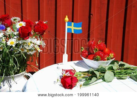 Swedish summer objects on a table outdoors by a red wall