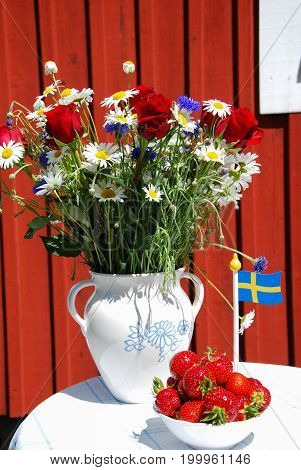 Flowers flag and strawberries - swedish summer decorated table in front of a red wooden wall
