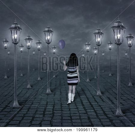 The girl with a purple balloon is walking among the street lights at night.