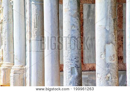 Detail of several aged marble columns in a row.