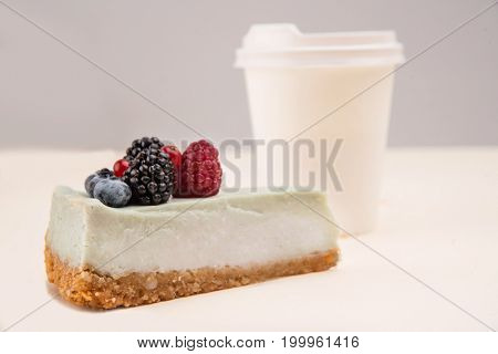 Blue cheesecake wit berries standing near paper cup isolated