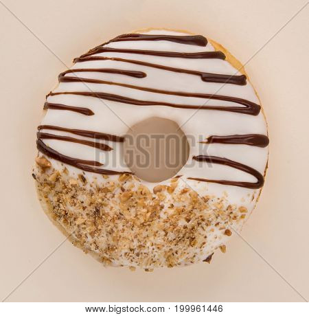 Top view of delicious donut with nuts and white cream isolated over white
