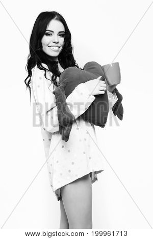 pretty woman or cute sexy girl with long brunette hair and smiling face in nightie shirt holds red pillow heart and coffee or tea cup isolated on white background
