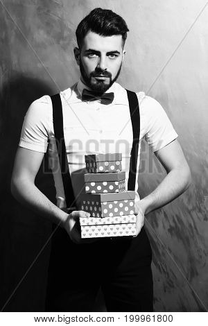 bearded man long beard brutal caucasian hipster with moustache in white shirt and suspenders with bow-tie holding present boxes with serious face on brown studio wall background