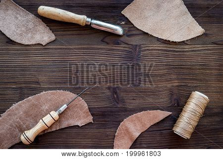 Tanner's workplace. Tools and matherials on dark wooden table background top view.