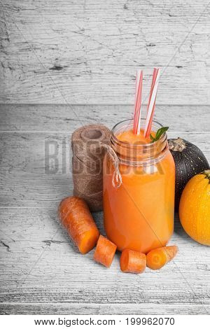A composition of natural ingredients on a rustic wooden background. Coil of threads, delicately cut carrot and round zucchinis next to a jar of bright orange carrot juice with straws. Copy space.