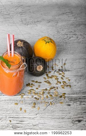 A transparent bottle filled with orange carrot beverage and three multi-colored zucchinis on a light table background. Vegetables and nutritious pumpkin seeds for vegan cooking.