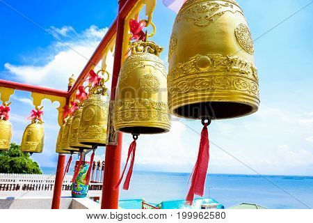Golden bells in shrine with blue sky and sea view