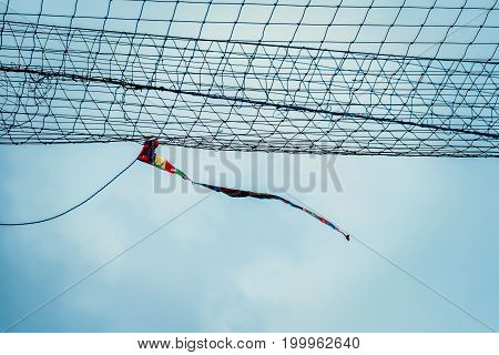 Rag tied to the net blowing in sport field similar to windsock to show the direction and strength of the wind against cloudy sky in the blue day
