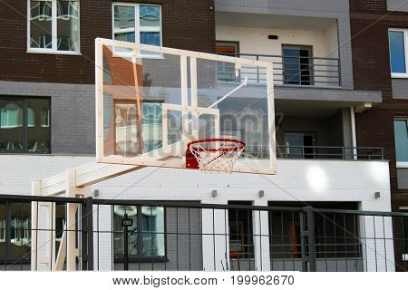 Basketball Hoop In A Residential Yard In The Background Of A Skyscraper