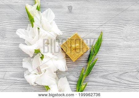 Celebration accessories. Box in golden paper near flower gladiolus on light wooden table top view.