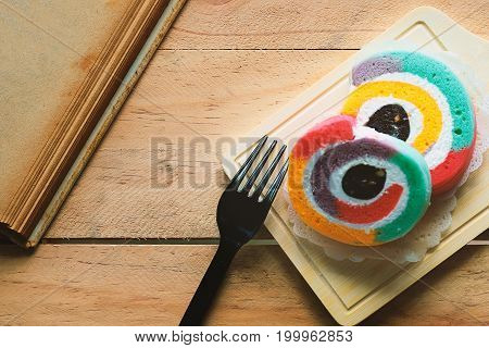 Rainbow color of yam roll bakery with a book on the wooden table