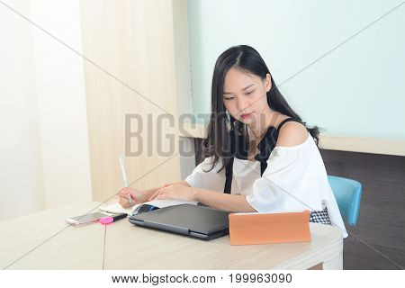 Asian Woman Concentrated Working Hard In Office