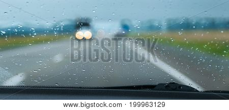 Blurred traffic lights seen through the rain drops on the windscreen of a car on a highway