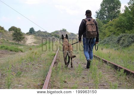 A master and his Malinois Belgian shepherd who walks along the rails