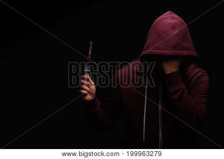 Addict male with a syringe full of drugs on a saturated black background. A hopeless drug addict is going through addiction crisis. Fear, depression, abuse, addiction concept.