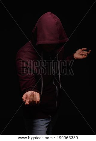 Alcohol addicted man in the hood on a saturated black background. A sad depressed male adult having troubles with alcohol. Alcoholism and unhealthy concept.