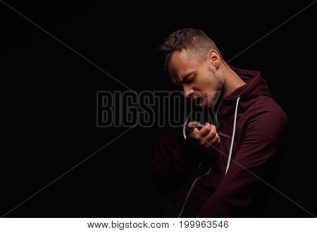 A suffering, narcomaniac guy with a full syringe on a black background. A young man in pain, obsessed with narcotics killing himself with a syringe. Social problems and deadly addiction concept.