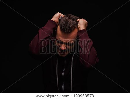 Furious, angry, freaky guy in a loose red sweater on a black background. A sick guy screaming, holding his head and clenching fists in self-loathing. Obsession, drug cravings, addiction concept.