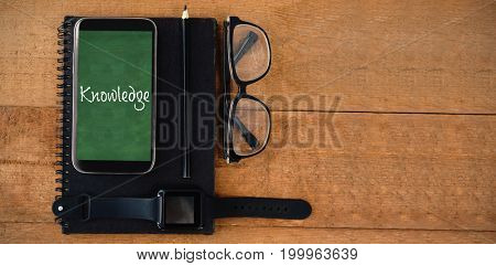 Knowledge text against white background against personal accessories on wooden table