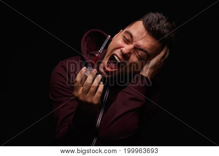 A narcomaniac guy in a dark hoodie, holding a syringe and screaming on a black background. A young man fighting with drug cravings. Cocaine, meth, cannabis, LSD, ecstasy, morphine addiction concept.
