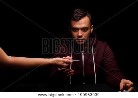 Drug-dependent with a syringe. A close-up picture of a guy with a drug addiction on a black background. Liquid ecstasy in a syringe. Young man in a wine colored jacket. Drug concept. Copy space.