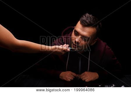 Liquid ecstasy in a syringe. A close-up picture of a narcomaniac on a black background. Drug-dependent with a syringe. Young man in a wine colored jacket. Drug, mania concept. Copy space.