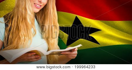 Happy student against digitally generated ghana national flag